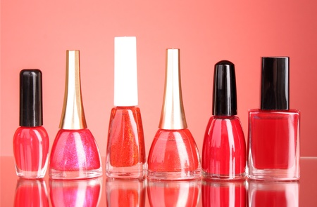 Group of nail polishes on red background photo