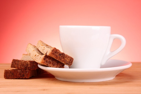 Cup of coffee and rusk on red background photo