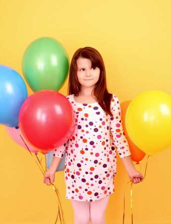 Little girl with balloons on yellow background Stock Photo - 9784442