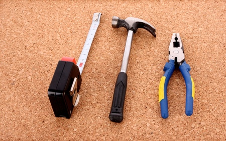 Hammer, pliers and ruller on cork board surface Фото со стока