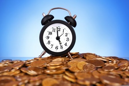 Alarm clock with golden coins on blue background Stock Photo - 8769717