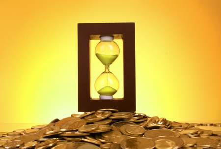 Hourglass and coins on yellow background photo