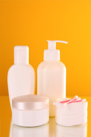bottles of health and beauty products on yellow background photo
