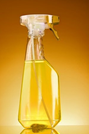 yellow spray bottle on brown background photo