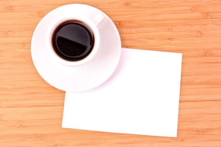 Coffee and blank paper on wooden surface photo