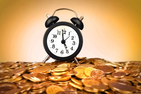 Alarm clock with golden coins on yellow background Stock Photo - 8914486