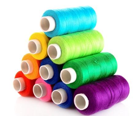 thread: Pyramid of many-coloured bobbins of thread isolated on white