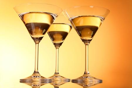 Three martini glasses on yellow background Stock Photo