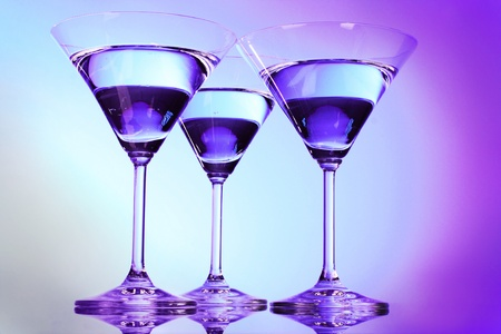 Three martini glasses on purple background photo