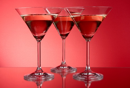 Three martini glasses on red background photo