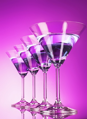 martini splash: Four martini glasses on purple background Stock Photo