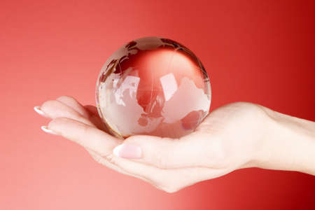 Crystal ball on hand. Red background photo