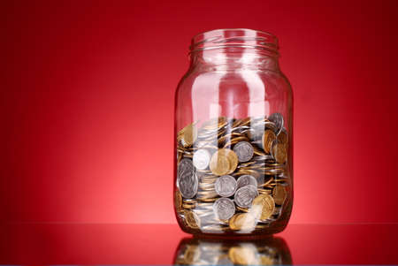 money jar: coins in money jar on red background. Ukrainian coins Stock Photo