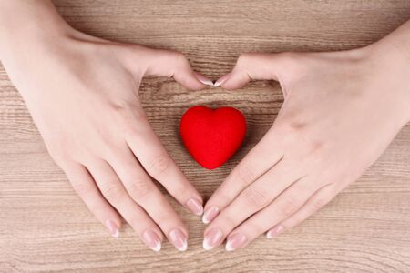 red heart in hands on wooden background Stock Photo - 9005261