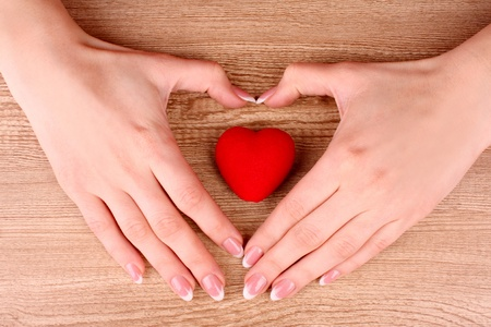 red heart in hands on wooden background Stock Photo - 9005325