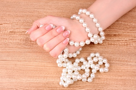 Woman hand with pearls on wooden background photo