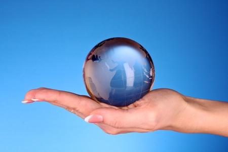 bola de cristal: Bola de cristal en la mano. fondo azul