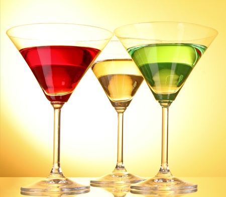 few: a few glasses of alcoholic drinks in a yellow-brown background Stock Photo