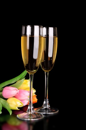 Glasses with champagne on black background with tulip flowers photo