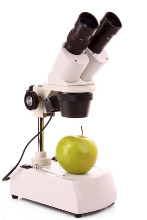 Green apple and microscope isolated on white photo
