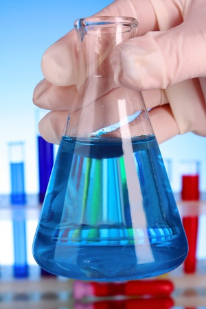 Conical flask with blue liquid on blue background with test-tubes photo