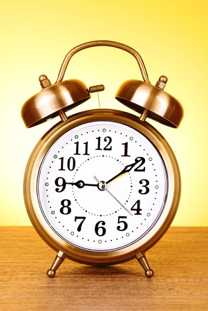 Old alarm-clock on yellow background photo