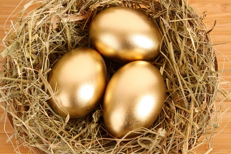 Three golden hens eggs in the grassy nest on the wooden table photo