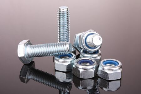 Screw and bolt with reflection on grey background photo