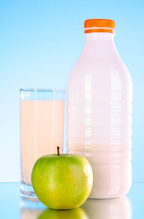 Bottle of milk and apple on blue background Stock Photo - 9132845