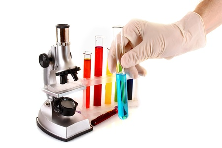 Laboratory metal microscope and test tube in hand with liquid isolated on white photo