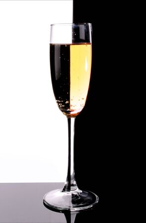 Glass with champagne on white and black background