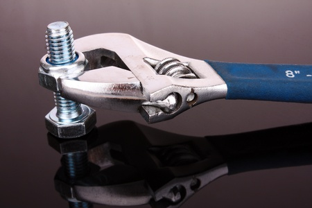 screwdriwer: adjustable wrench with nut on gray background