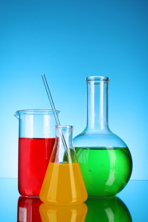 milliliters: Laboratory glassware on blue background Stock Photo