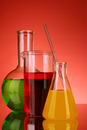 milliliters: Laboratory glassware on red background