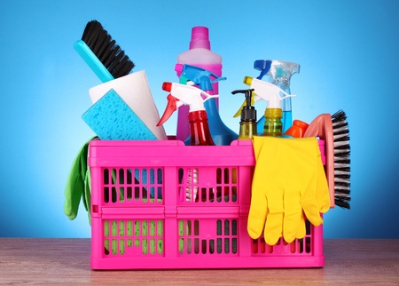 Cleaning supplies in basket on blue background photo