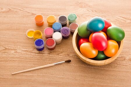 Colorful Easter Eggs, paints and brush on wooden table photo