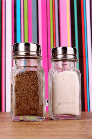 Salt and pepper shaker on color lines background photo