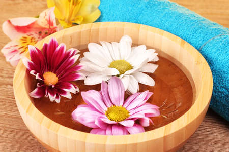 Pink and white flowers floating in bowl photo