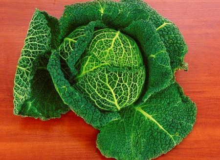 Savoy cabbage on wooden texture photo