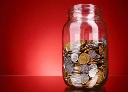 coins in money jar on red background. Ukrainian coins Stock Photo - 9281627