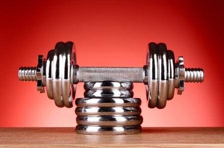 levantando pesas: Dumbbell sobre fondo rojo