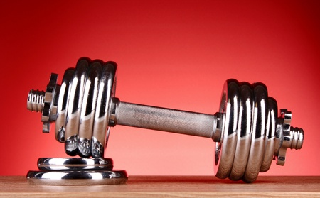 Dumbbell on red background photo