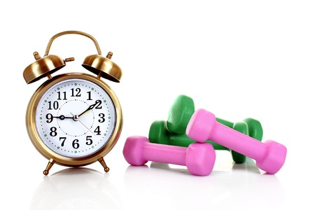 Old alarm-clock and dumbbells isolated on white photo