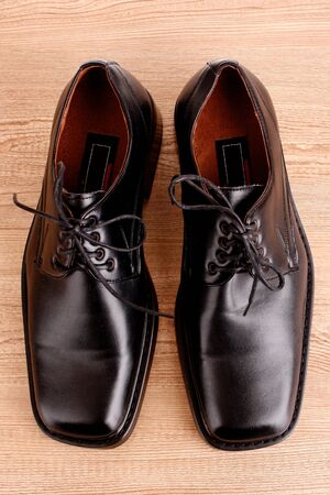 Mans shoes on wooden texture photo