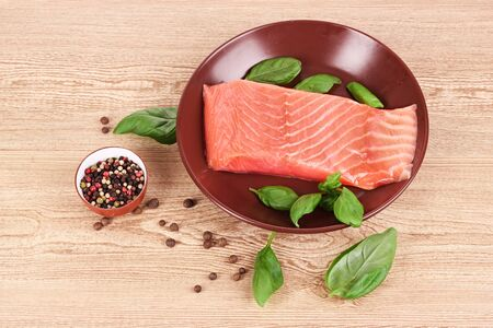 Red fish on the plate with pepper and green leaves photo