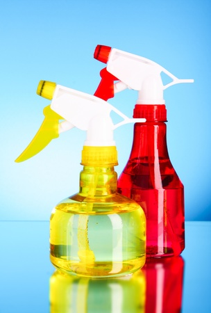 two spray bottles on blue background photo