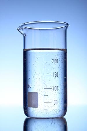 Graduated beaker on blue background photo