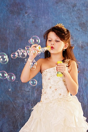 innocence: Little girl in white dress makes bubbles Stock Photo