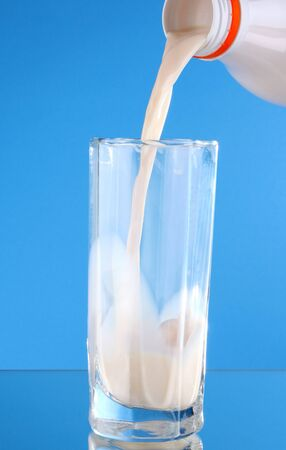 Someone pour milk in glass on blue background Stock Photo - 9365558