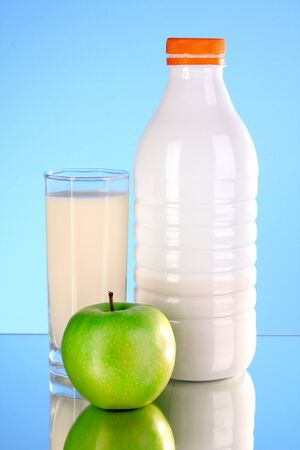 Bottle of milk and apple on blue background photo